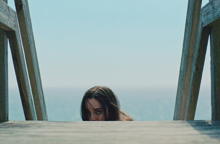 A woman crying, while climbing up wooden stairs from the film The Beach House.