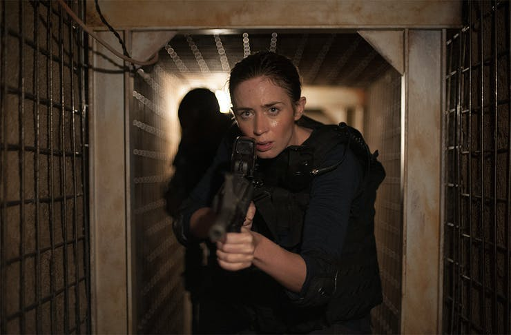 Emily Blunt advances down a corridor with gun in hand in a scene from John Wick