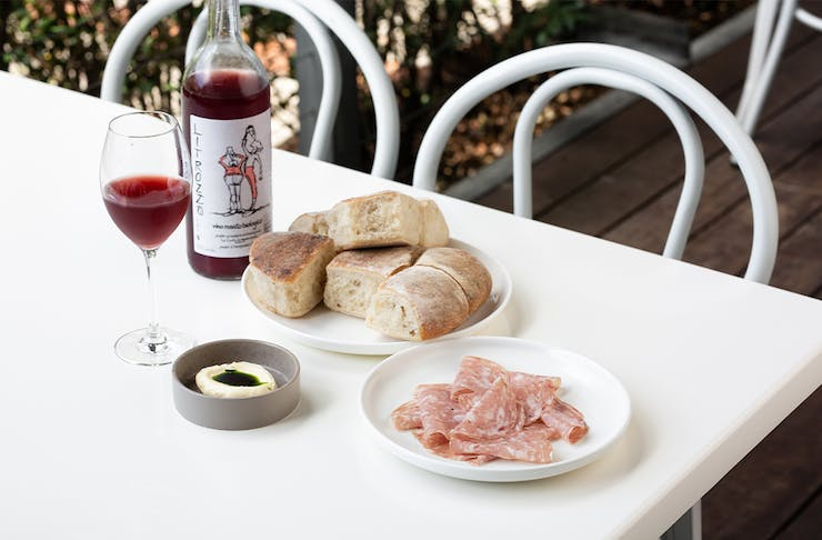 several small plates of snacks and a bottle of wine on a white table