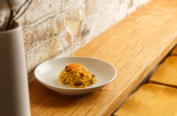 a bowl of spaghetti topped with fish roe and a glass of prosecco
