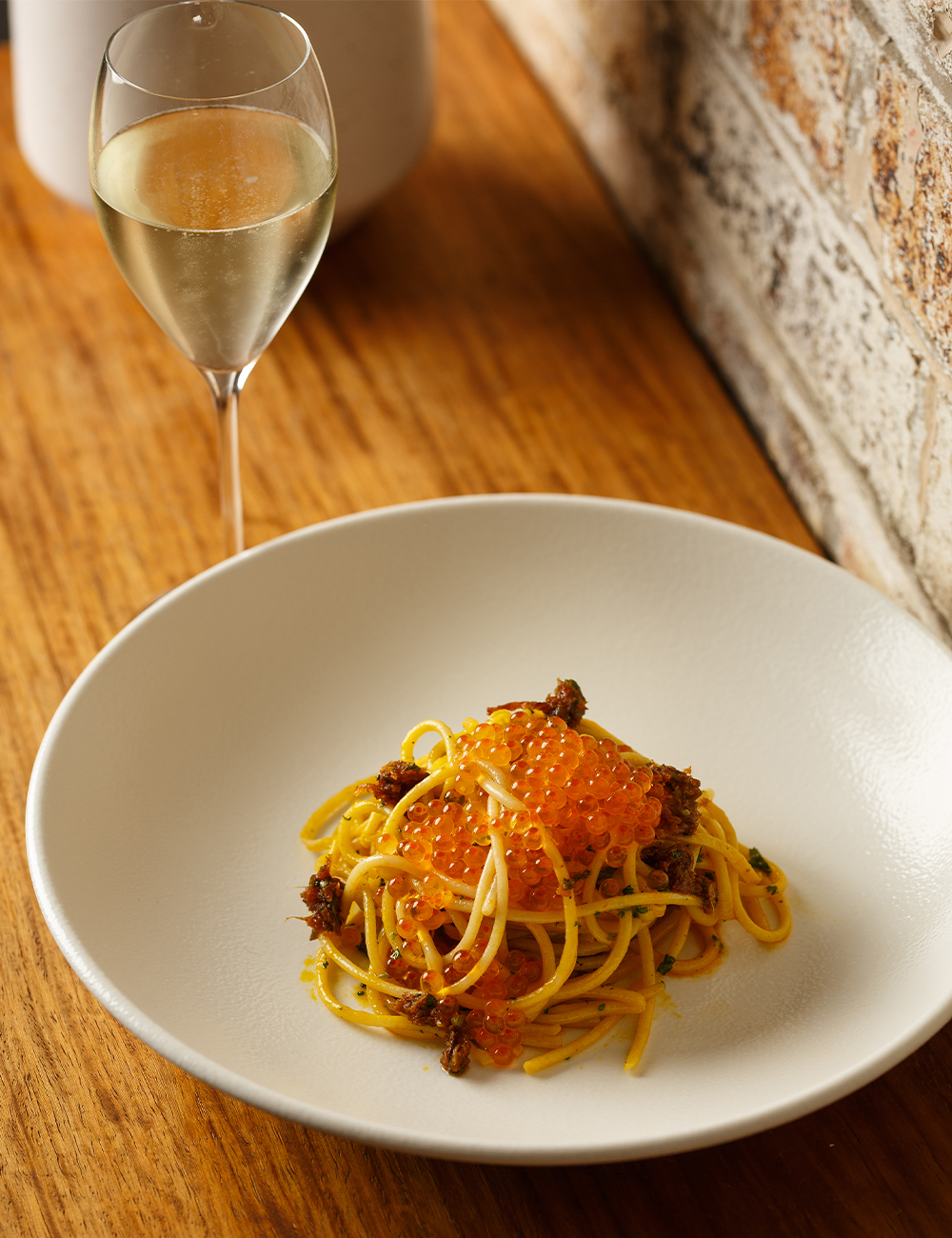 a bowl of spaghetti and a glass of prosecco on a bench