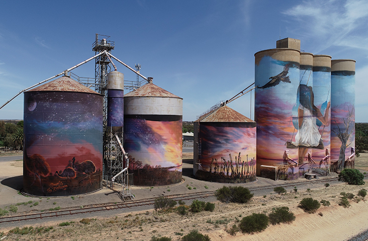 A silo with large art painted on it.