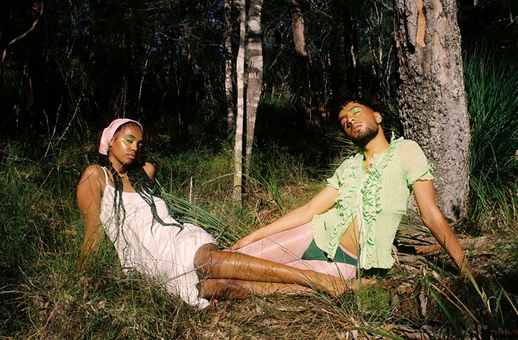 Two people wearing linen clothing and sitting in the grass, while basking in the sunlight.
