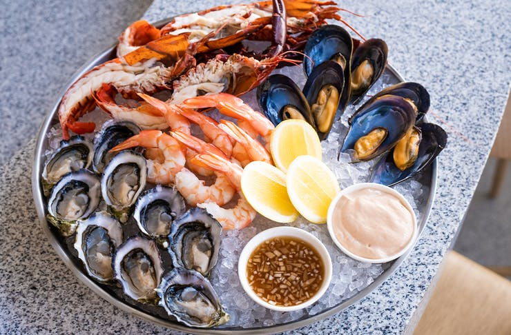 A large platter of mixed seafood on ice - prawns, mussels, oysters and bugs
