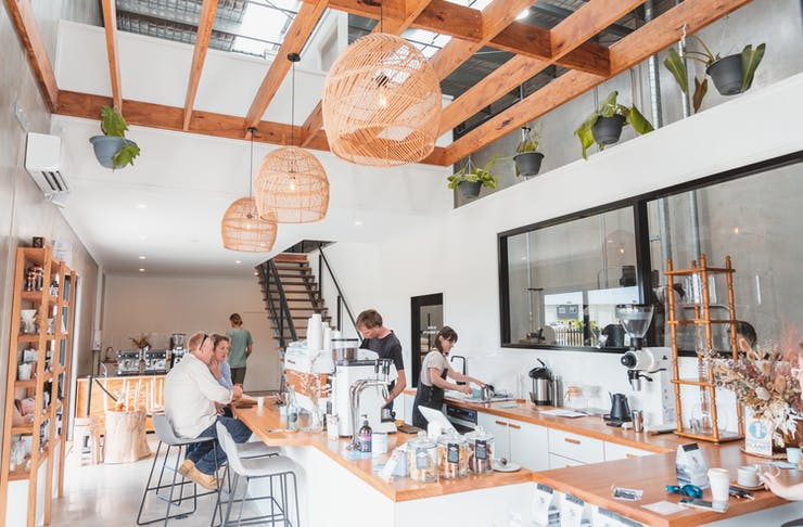 The brightly lit interior of Slide Coffee Roasters tasting room, with light wood accents and white walls and counter tops.