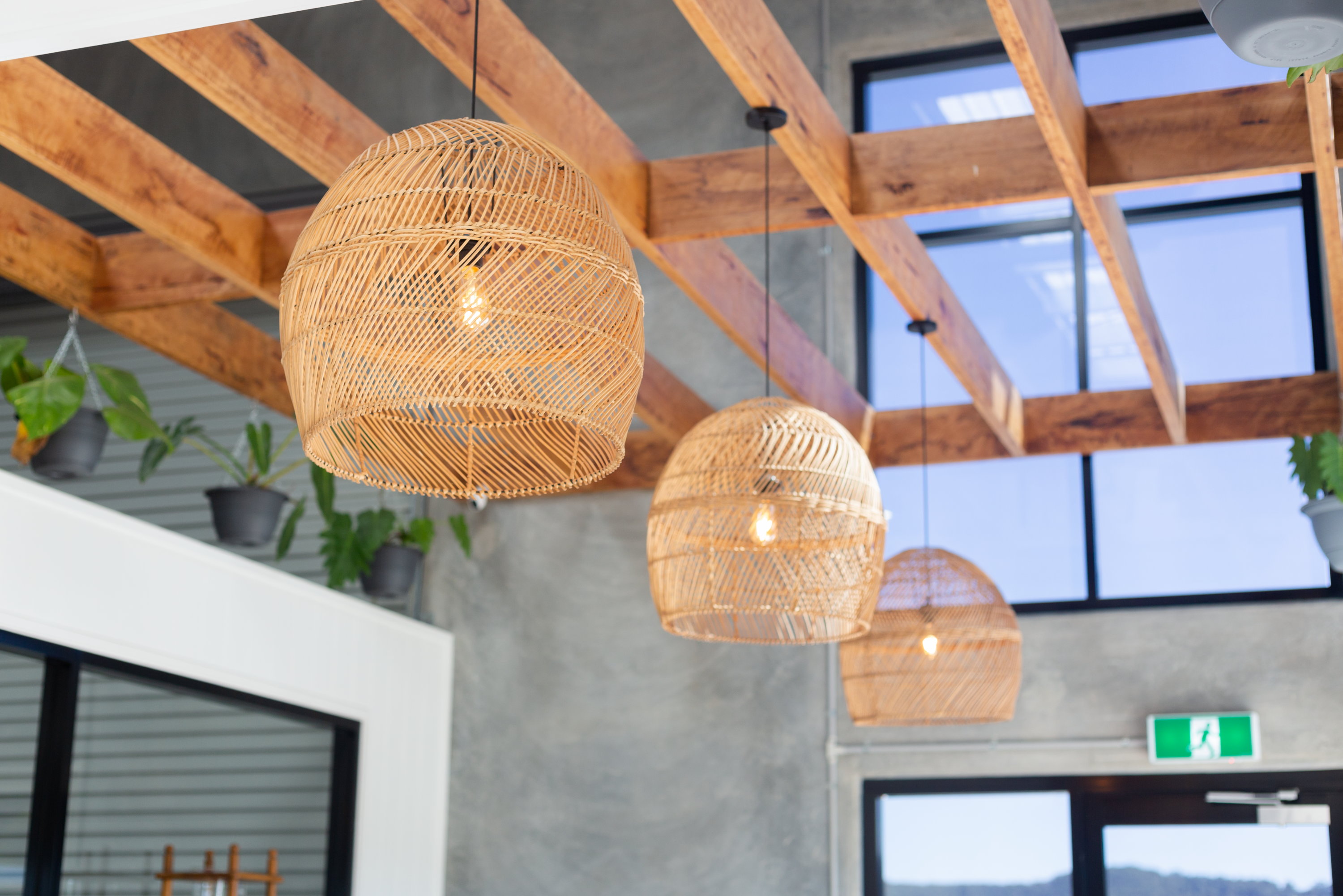 Wicker baskets around hanging bulbs against a varnished wood panelled ceiling.