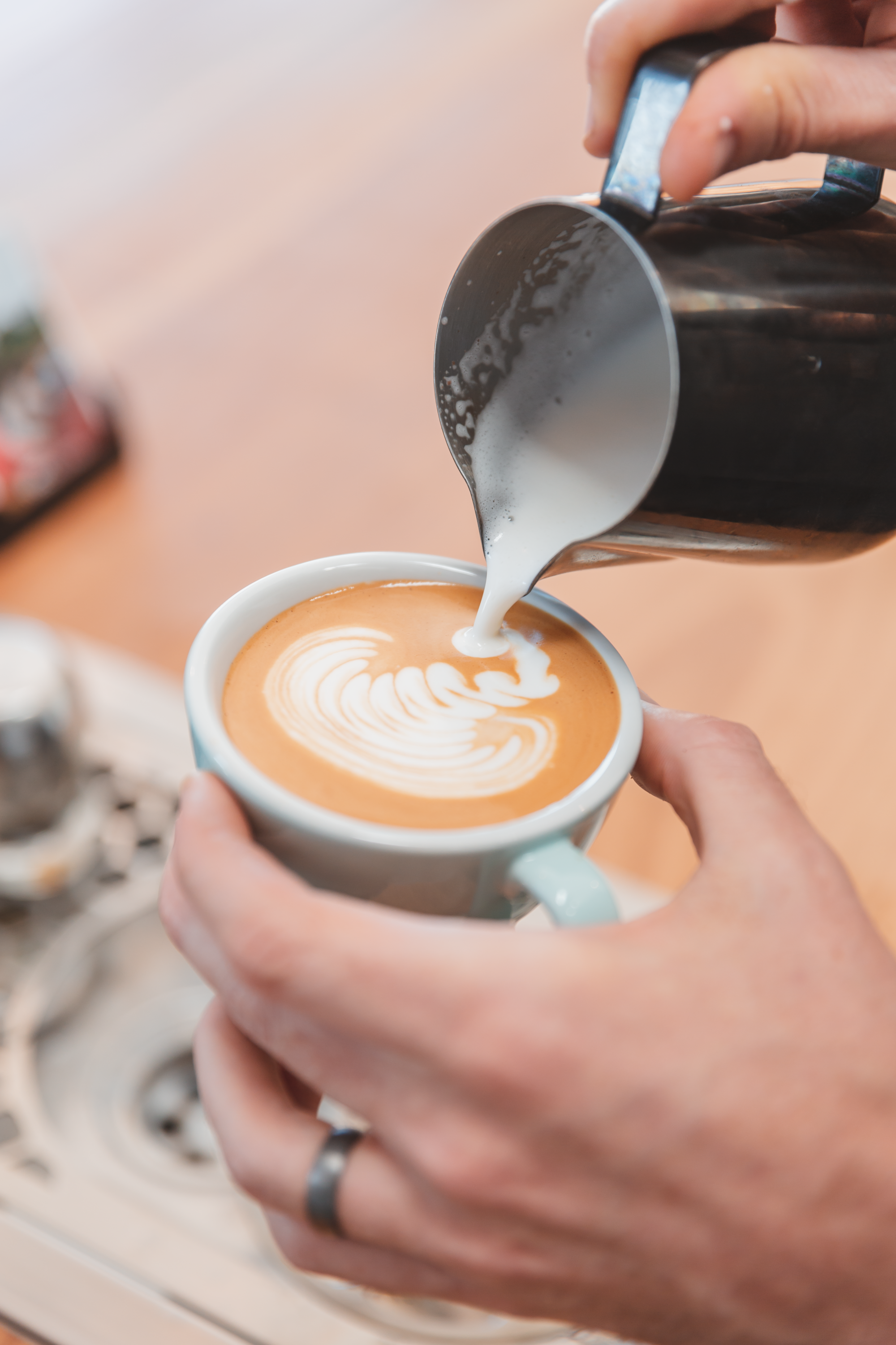 A hand holding a coffee cup and pouring milk into an artsy shape in the crema.