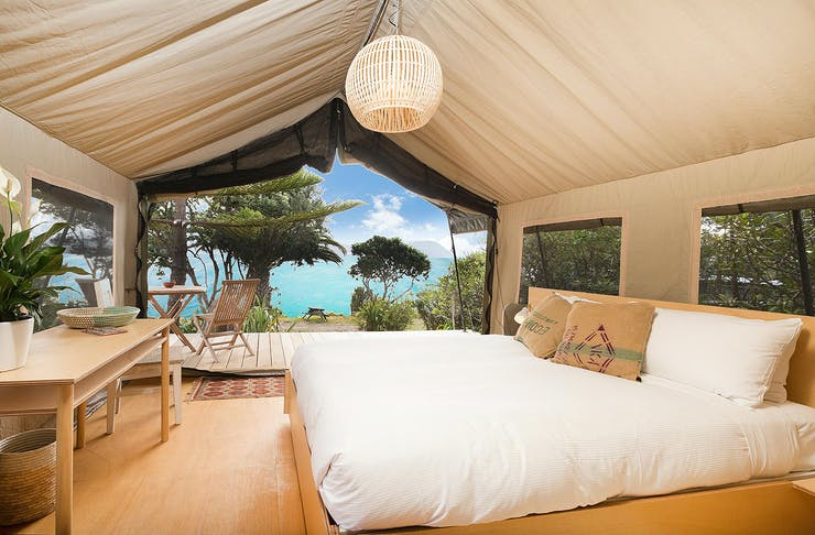 Glamping tent at slipper island looks out over impossibly blue sea.