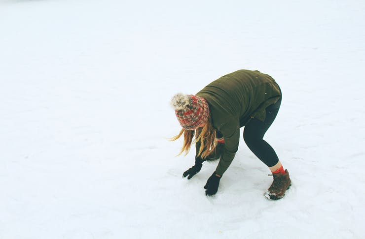 a woman picking up snow