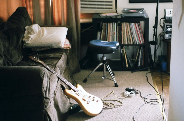 A cosy living room, with an electric guitar leaning against a couch and a shelf filled with old records.