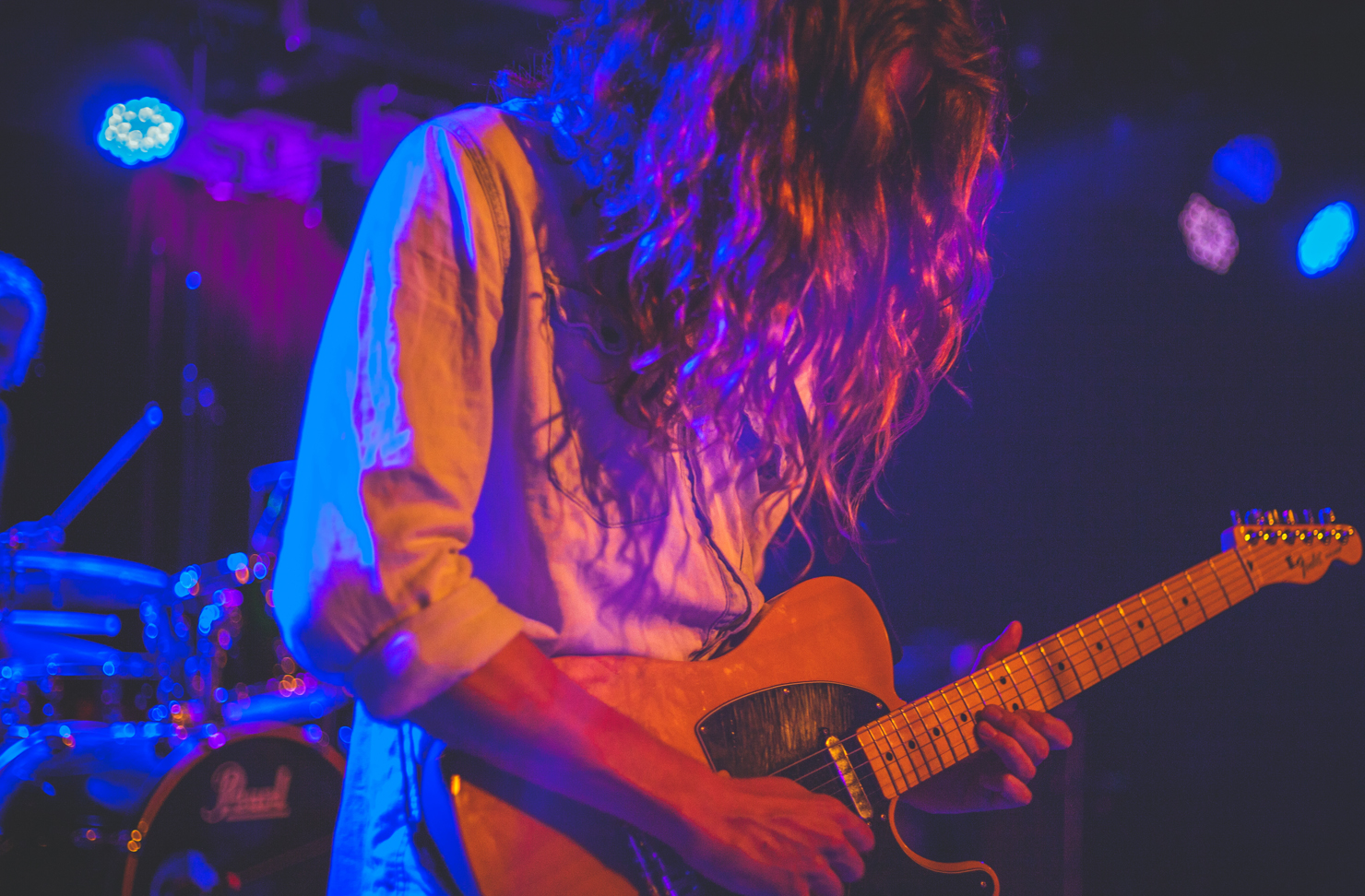 A musician on stage and playing guitar. Their face is covered by long, unruly hair.