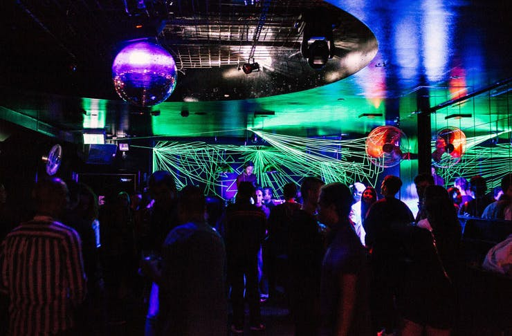 A busy dance floor with lasers and a disco ball.