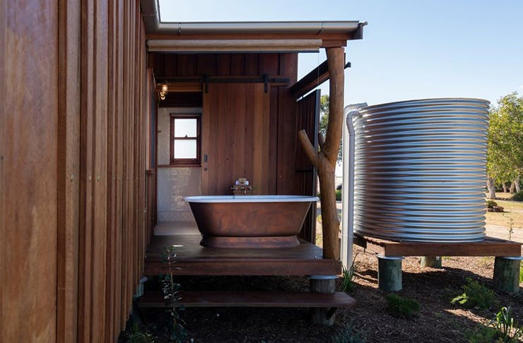 An outdoor brass bathtup next to a rain tank.