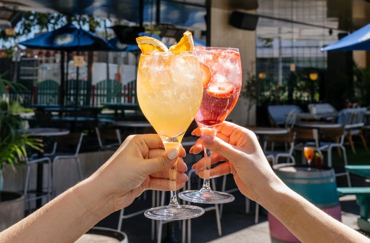 Two hands hold glasses of different coloured spritzes, one orange and one red.