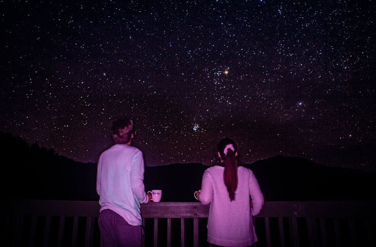 Two people stargazing with a view of the Southern night sky.