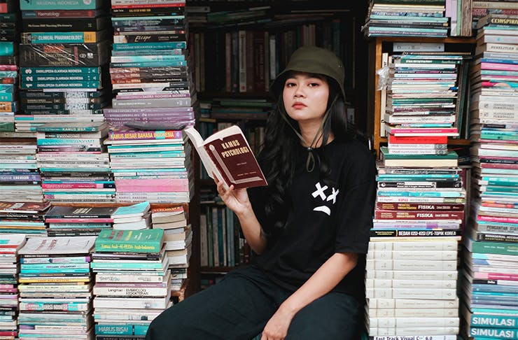 a woman wearing a hat holding a book and sitting between several large stacks of books