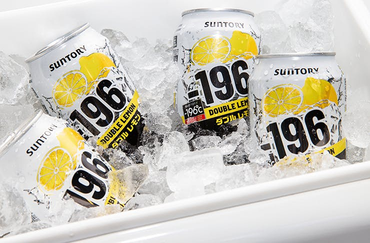 Four white and yellow cans of alcohol in a tub of ice.