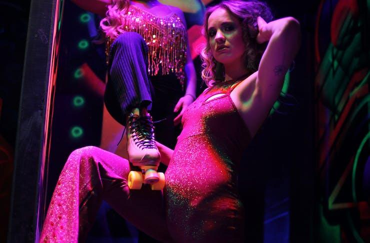Two girls pose in Studio 54 gear on rollerskates.