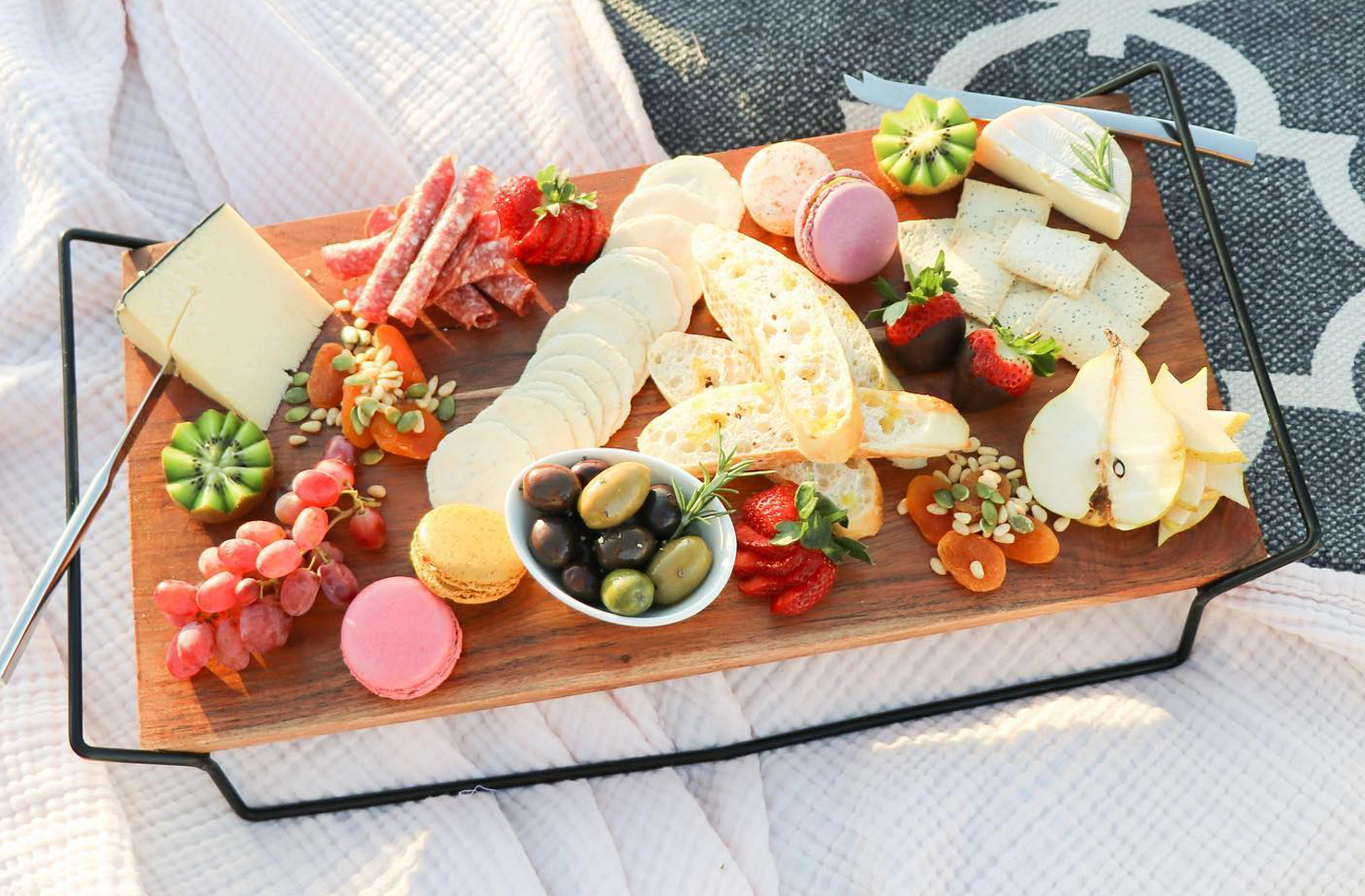 A picnic spread on a blanket, including cheeses, fruit, crackers, meats and nuts.