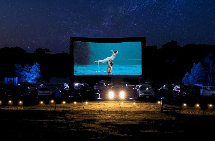 A drive in cinema at night with Dirty Dancing on the movie screen