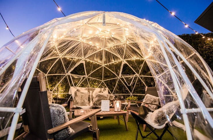 A pop-up plastic igloo with seating inside, sits at a Queensland pub.