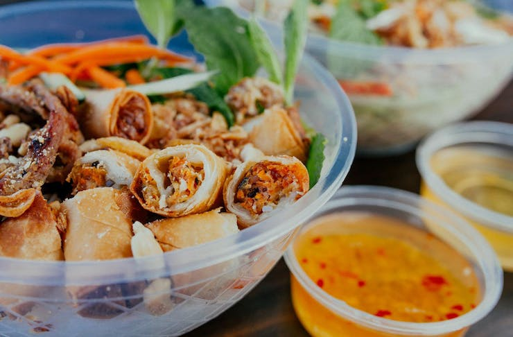 A spread of Vietnamese street food, including spring rolls and dipping sauces.