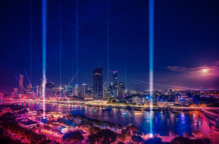 A view of the city skyline with lasers pointing to the sky