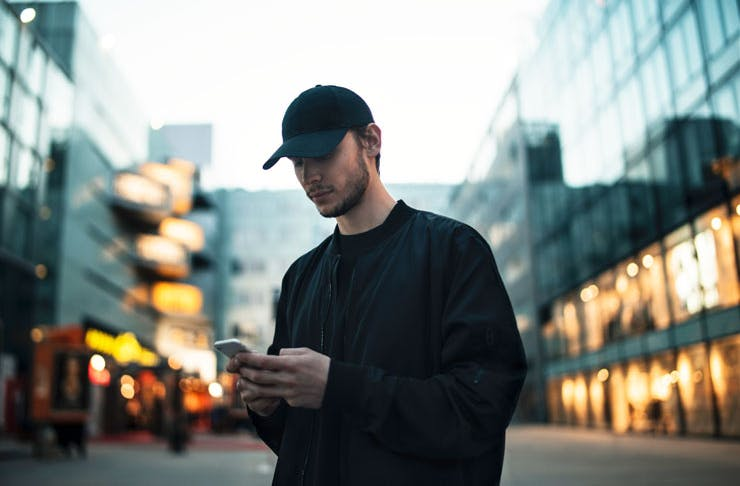 A man checking his phone on a city street at twilight.