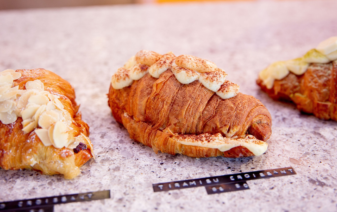 a row of croissants on a bench