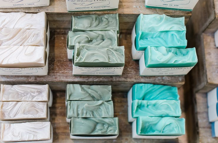 Different coloured handmade soaps on a wooden bench.