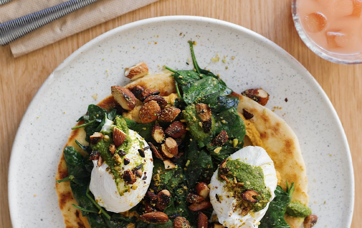 eggs and spinach on top of a fried flat bread