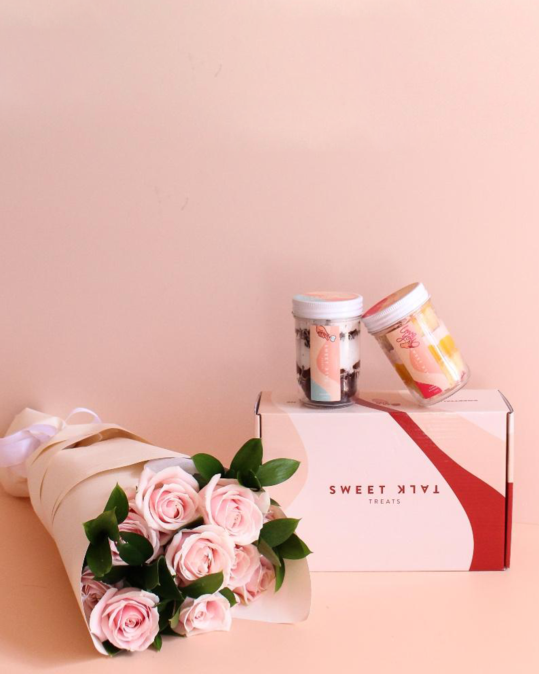 A lovely bouquet of blush roses sitting beside two decadent jars of layer cake.