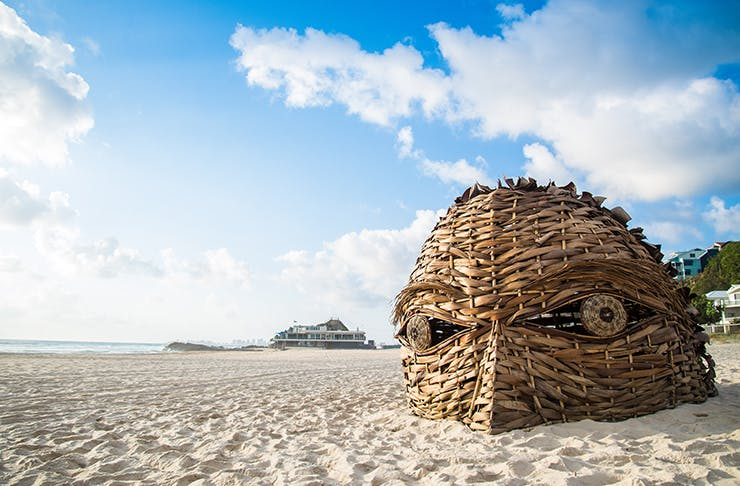 A giant woven sculpture of the top of a head laying in the sand.