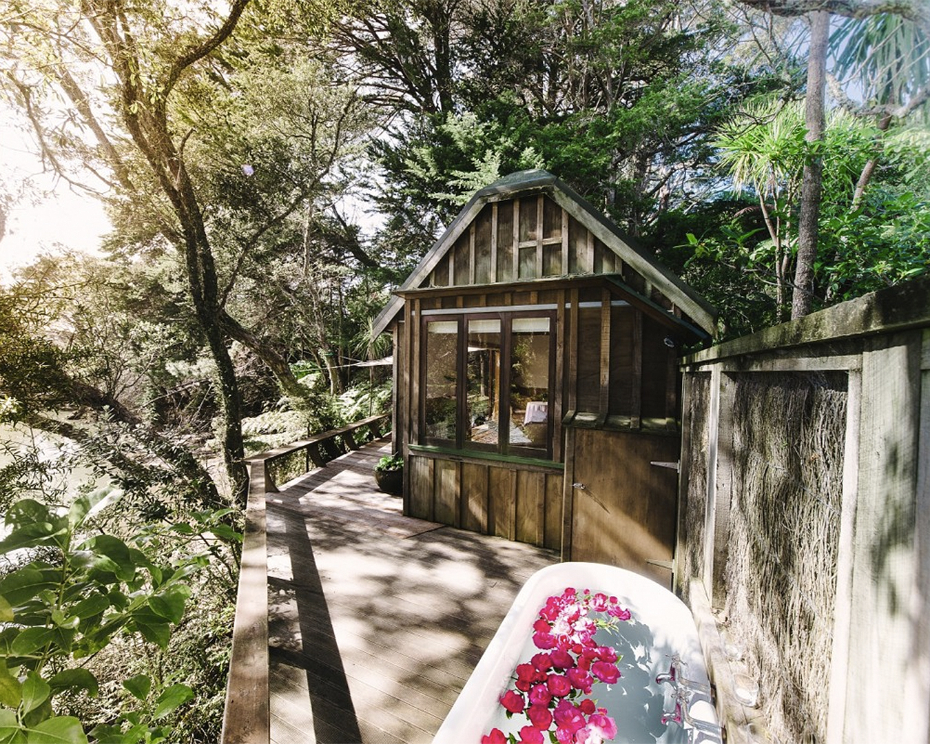 A view of a gorgeous looking cottage with a bath with petals outside.