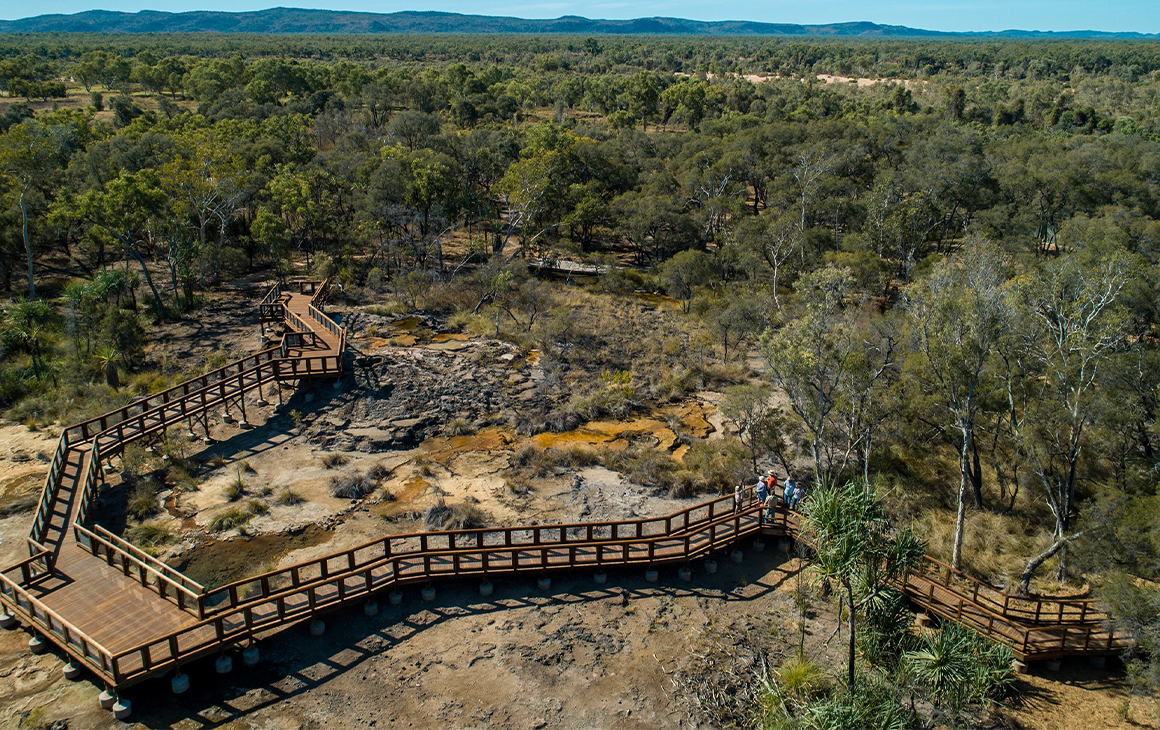 a wooden boardwalk crossing hot springs in the outback