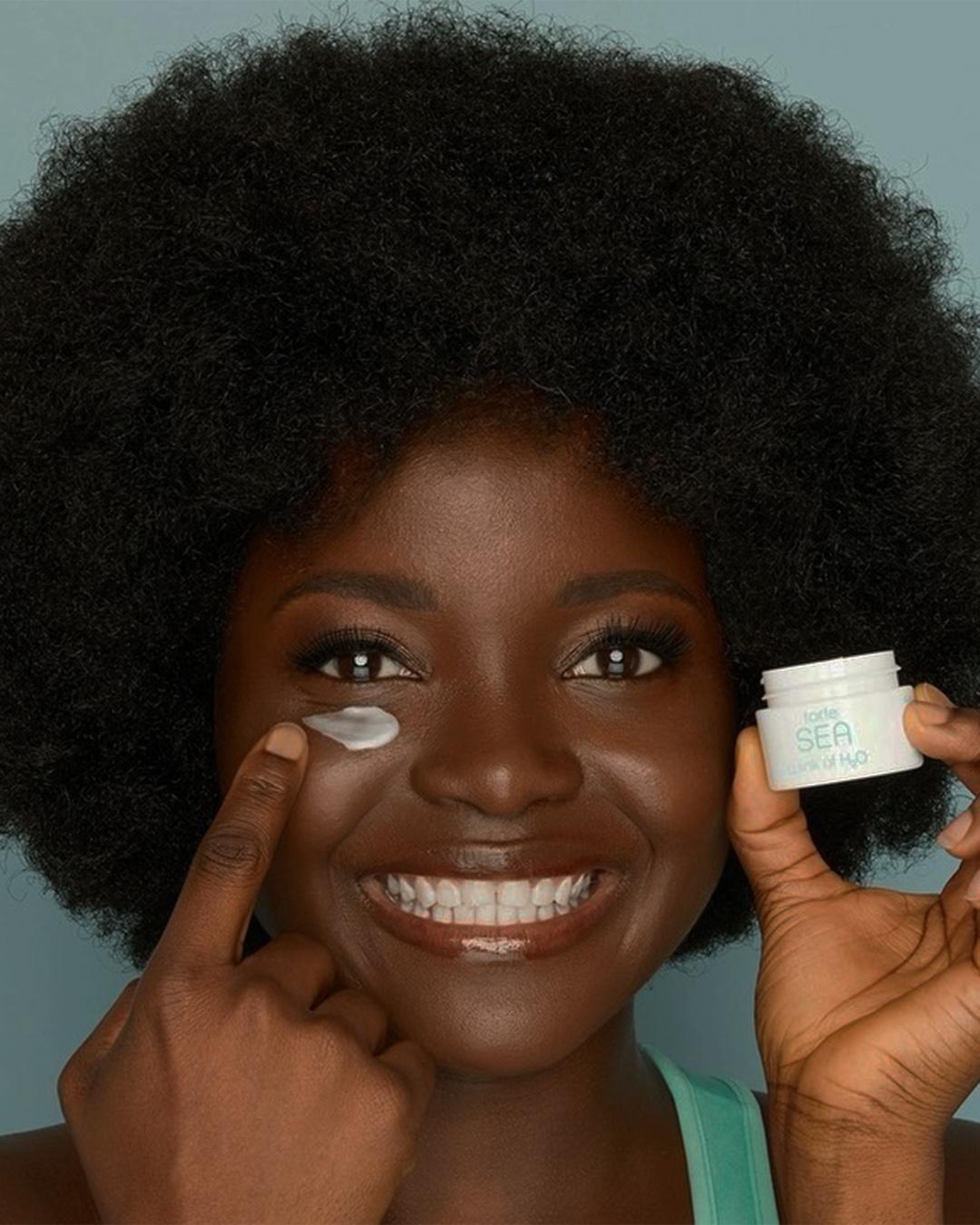 A model poses with Tarte, Sea, Wink H20 Vegan Collagen Eye Cream under one eye.
