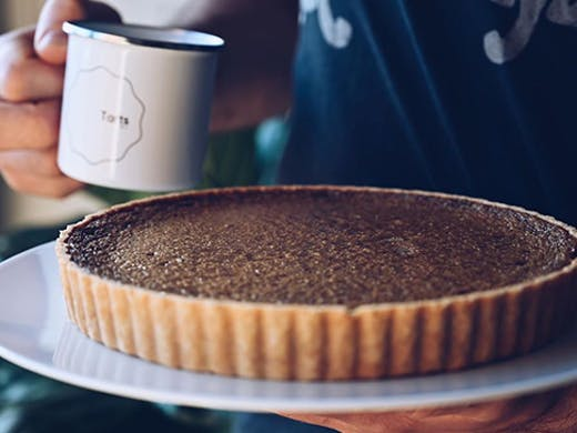 A tart on a plate next to a mug with a label that reads