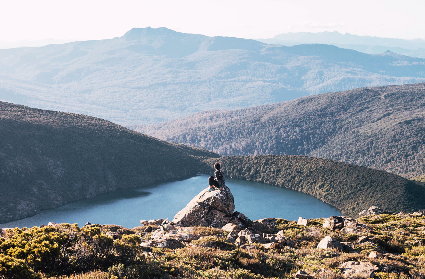 A woman takes in the view of rolling hills and a lake, from a mountain top in Tasmania.