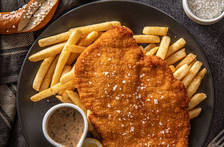 A plate of schnitzel with hot chips.