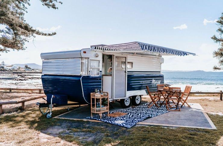 The Botanist Gin Caravan parked beside a sunny beach.