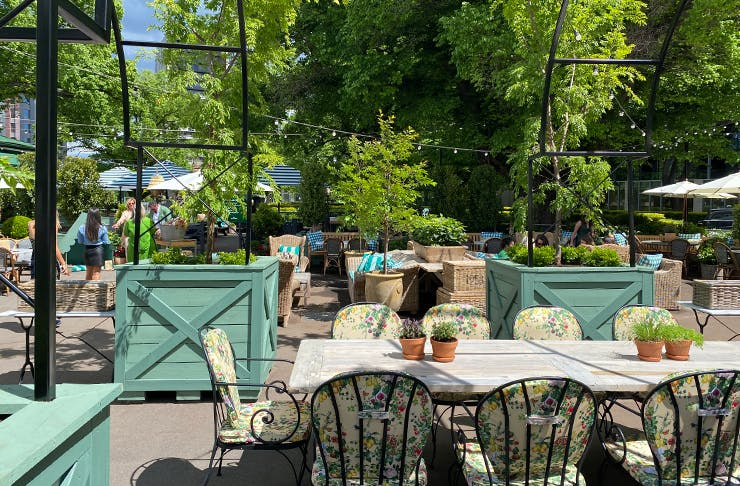 Tables and chairs in a lush, green outdoor bar setting.
