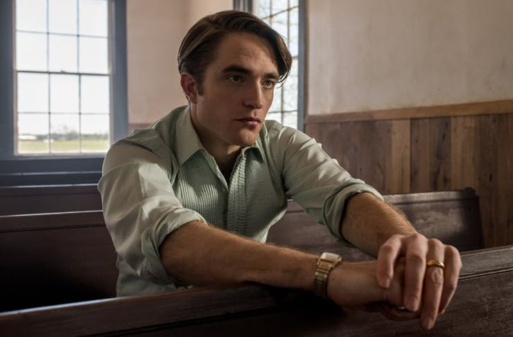 Robert Pattinson sitting in a church on the set of The Devil All The Time.