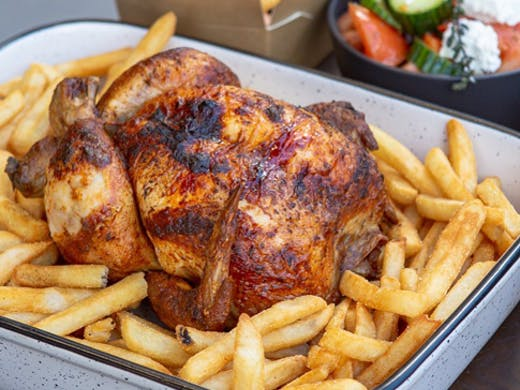 A rotisserie roasted chicken on a bed of chips from The Hot Bird in Cheltenham.