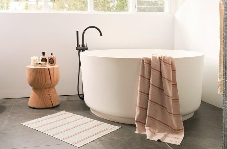A round-shaped bath draped with a rust-coloured towel