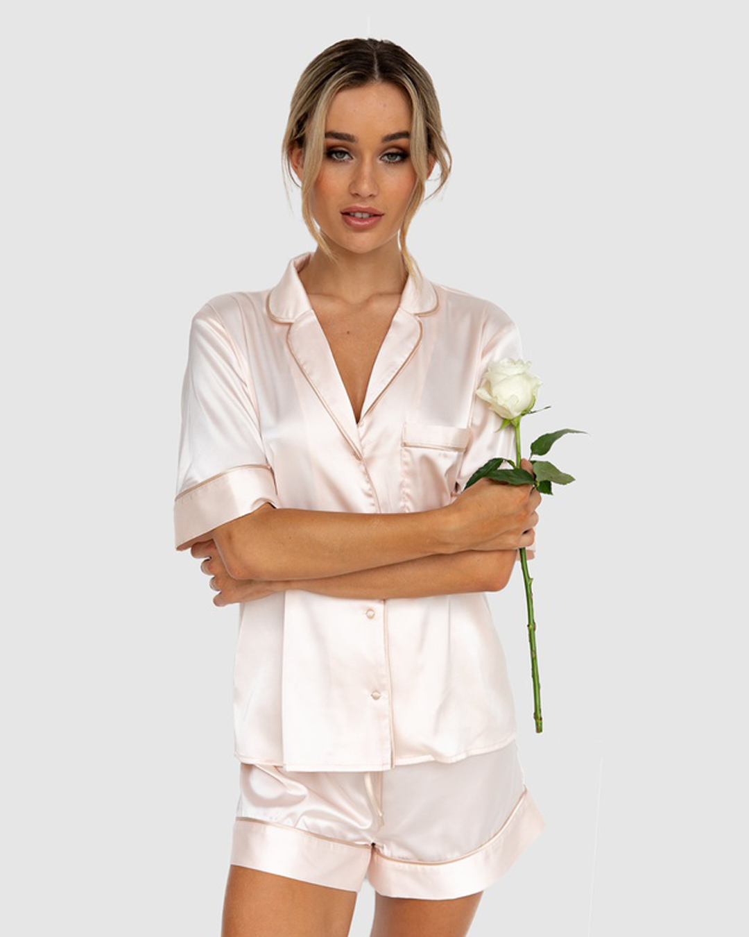 A model wearing pale blush satin pyjamas holding a rose