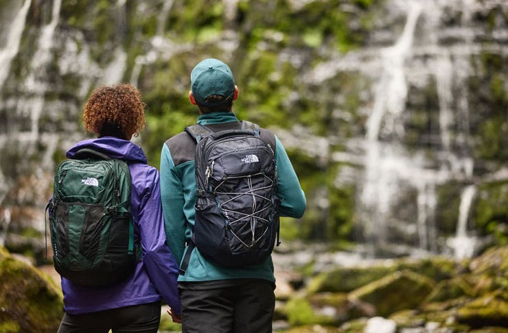 A couple in front of a waterfall with Th North Face backpacks