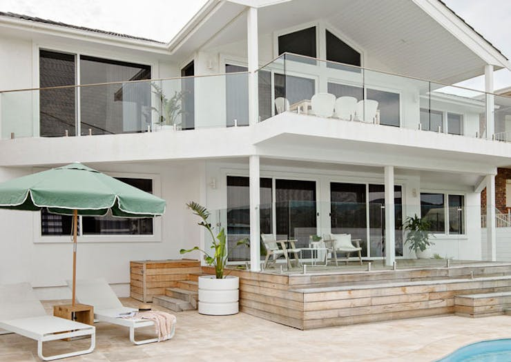 A large white beach house, with a pool in the foreground, deck chairs and a green umbrella.