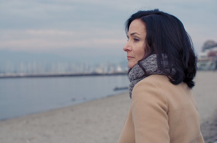 A woman standing on the beach looking pensively out at the water.