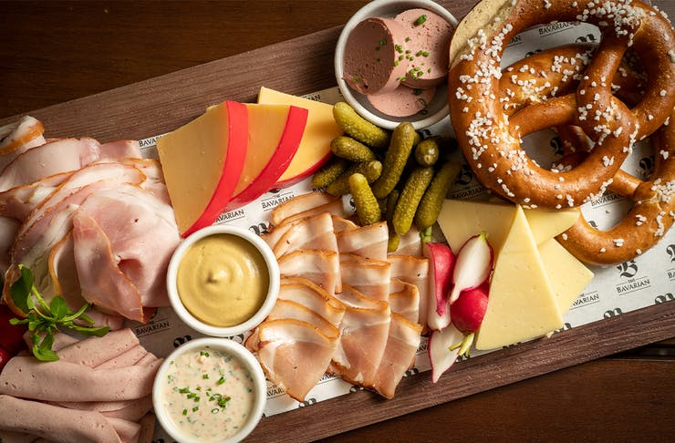 a board piled with various cold meat slices, cheese and pretzels