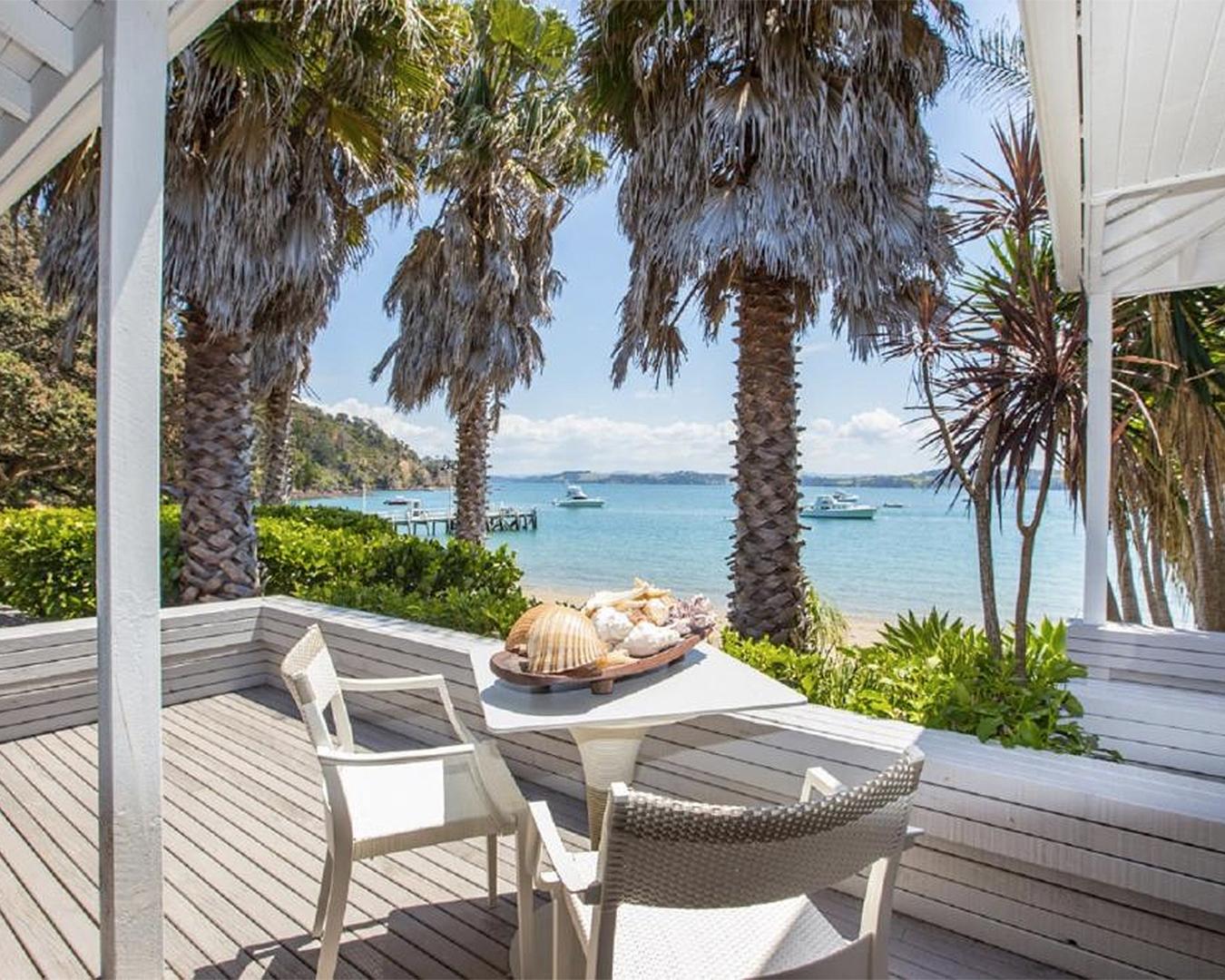 Two chairs overlook stunning sea at The Beach House on Kawau Island.